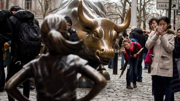 """People take photographs of the the """"Fearless Girl"""" statue as it stands across from the iconic Wall Street charging bull ..."""