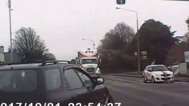 A frame from Annie King Holden's dashcam footage shows the moment another driver swerved their black car around her ...