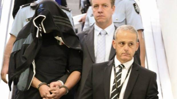 Detectives escort Diego Carbone out of Sydney International Airport after his arrest in 2014.