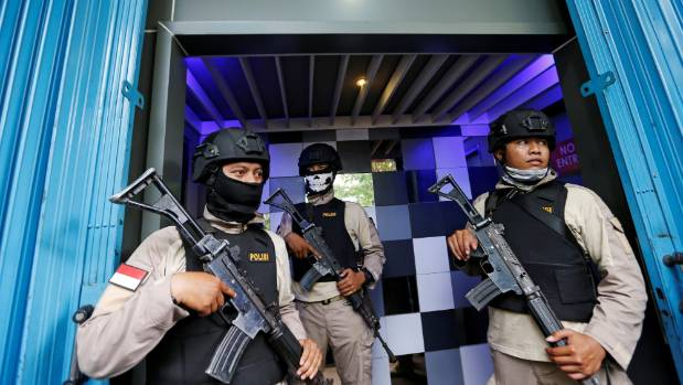 """Policemen hold rifles during the weekend raid on a """"gay spa"""" in Jakarta."""