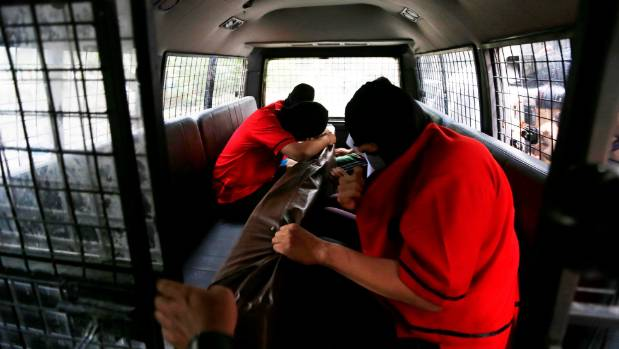 Detainees hold items from a men's club in a police vehicle after the police conducted a weekend raid on what authorities ...
