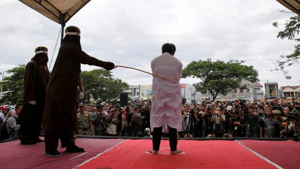 An Indonesian man is publicly caned for having gay sex in Banda Aceh, in May.