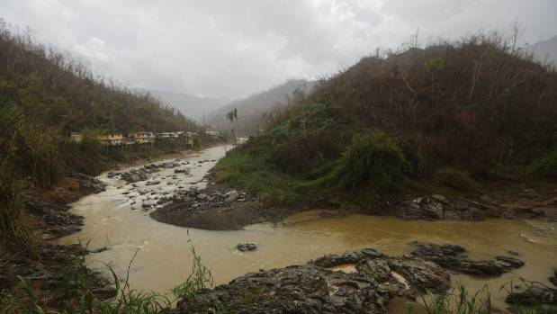 Damaged homes stand above a river nearly three weeks after Hurricane Maria hit the island.
