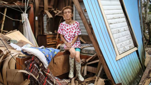 Sonia Torres poses in her destroyed home, while taking a break from cleaning, three weeks after Hurricane Maria hit ...