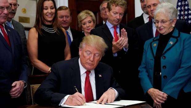 US Senator Rand Paul applauds as US President Donald Trump signs an executive order to make it easier for Americans to ...
