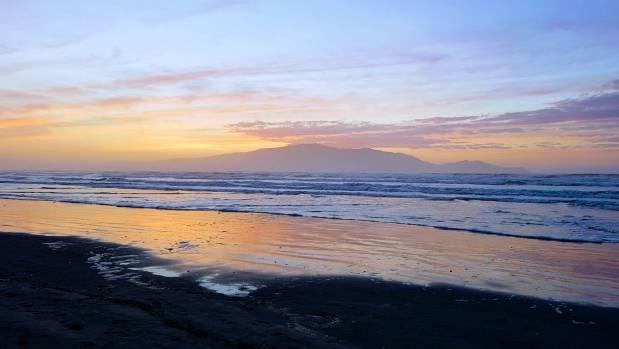 A stunning spring sunset over Waikanae Beach creates a beautiful backdrop behind Kapiti Island.