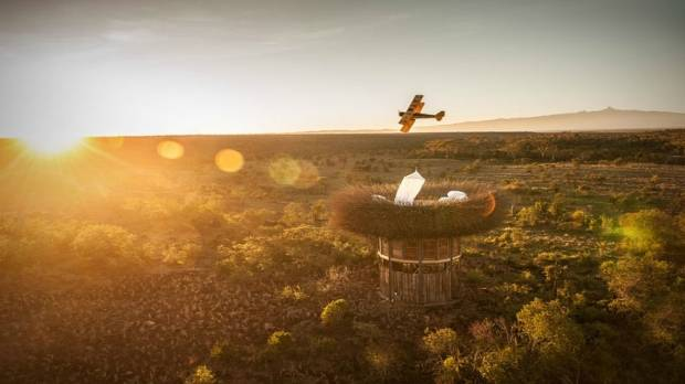 A biplane circles the giant bird nest at the Segera Retreat.