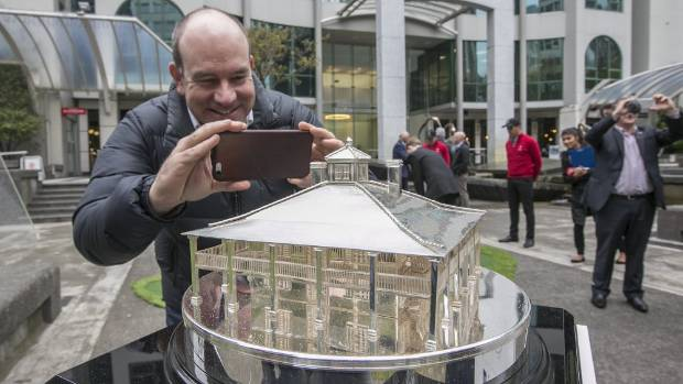 Josh Tabor snaps a picture of the Masters trophy, in Midland Park to promote the Asia-Pacific Amateur Championship at ...