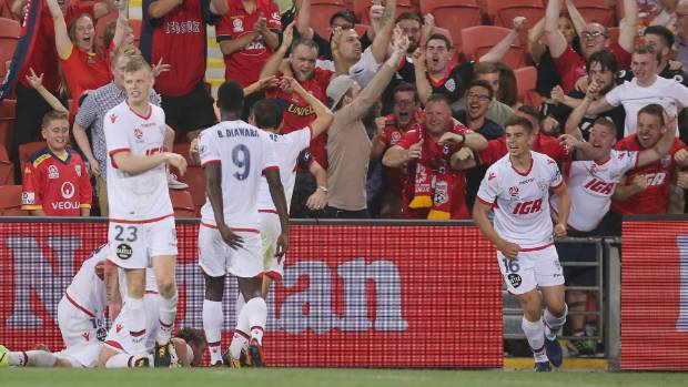 Adelaide United players celebrate their eualising goal from Ryan Kitto in their 2-1 victory over the Brisbane Roar.