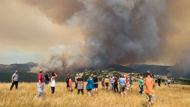 Onlookers above Westmorland were moved on by police as flames leapt out of a large pine plantation behind Worsleys Road properties consumed by the huge fire on the Port Hills. — Photograph: Joseph Johnson.