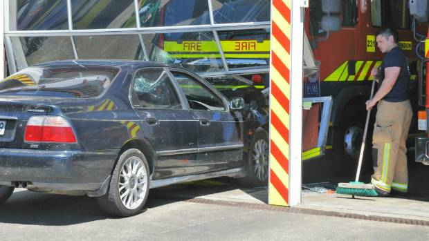 A firefighter sweeps broken glass after a Honda Accord smashed into the front of Porirua Fire Station on November 6.