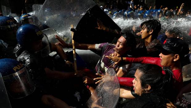 Protesters clash with anti-riot police officers as they try to march towards the US embassy in Manila Philippines