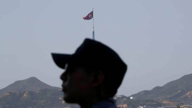 A South Korean soldier stands guard as a North Korean flag flutters on top of a tower at the propaganda village