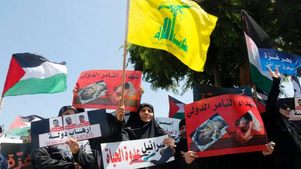 Lebanon's Hezbollah supporters hold banners and wave Hezbollah, centre, and Palestinian flags, left, during a ...