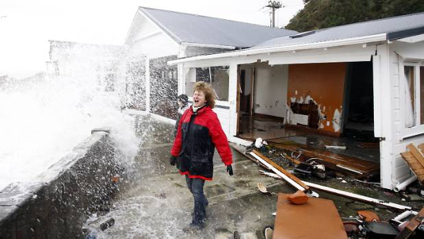 Days Bay resident Sarah Gilbert checks out the weather in a 2013 storm. Katherine Mansfield's holiday beach house was badly damaged during the storm. Getting insurance could become a major problem for residents of the Lower Hutt suburb of Eastbourne.