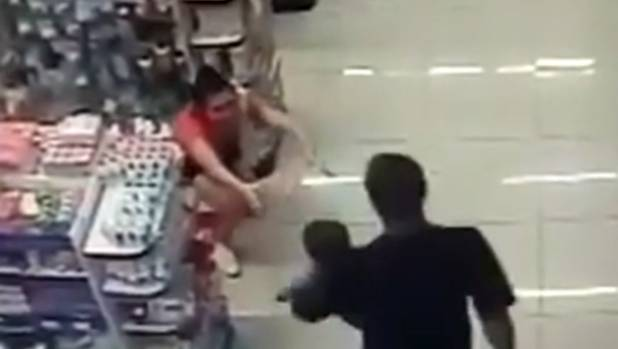 At one point the officer is seen handing the baby to his wife who had taken cover behind one of the store's aisles