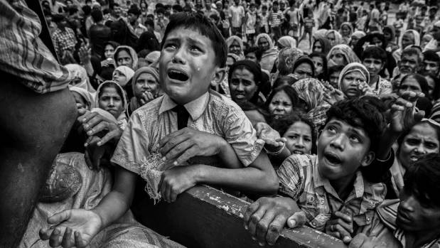 A Rohingya refugee boy desperate for aid cries as he climbs on a truck distributing aid for a local NGO near the ...