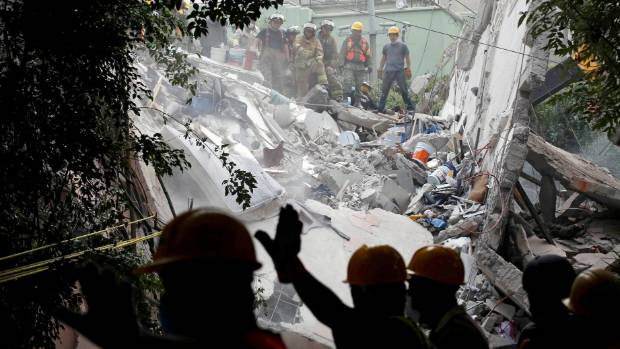 Soldiers and rescue workers search in the rubble of a collapsed building after an earthquake in Mexico City, Mexico ...
