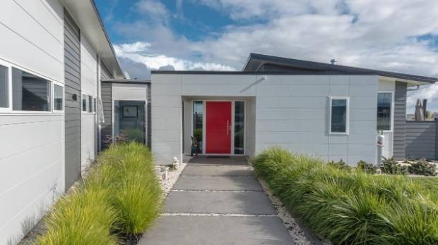 The red door is a bold colour accent for the house, which features contrasting grey tones.