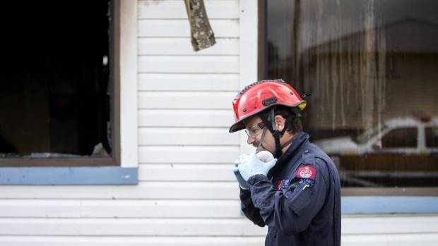Specialist fire investigator Andrew Cotter puts on protective equipment before entering the house.