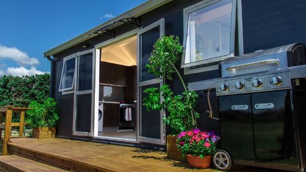 Tiny homes take on a more permanent look once a deck is added and the owner settles in with a barbecue and a few pot plants.