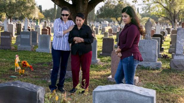 Irma Aragon, centre, visits the grave of her son, Alfed Aragon, in San Antonio. She is flanked by her daughter Yolanda ...