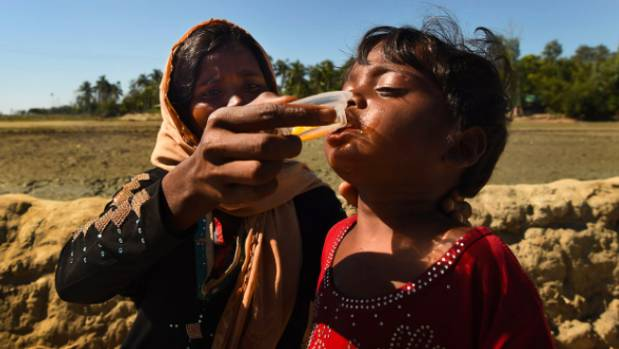A mother feeds her exhausted child a jelly drink as they make their way to a refugee camp.