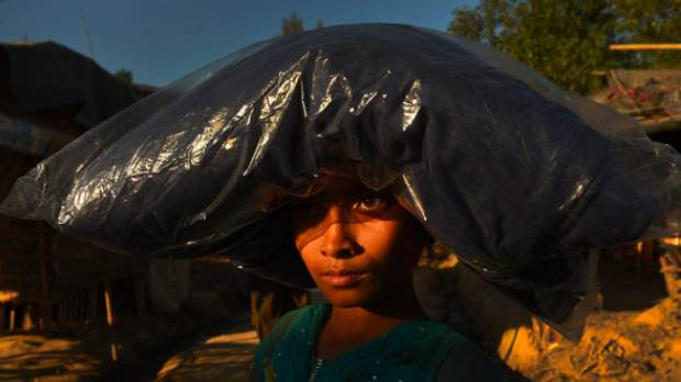 A Rohingya girl carries a blanket she has received in Burma Para refugee camp.