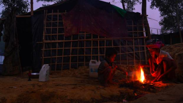 Two boys start a fire to cook breakfast outside their family shelter in Kutupalong camp.