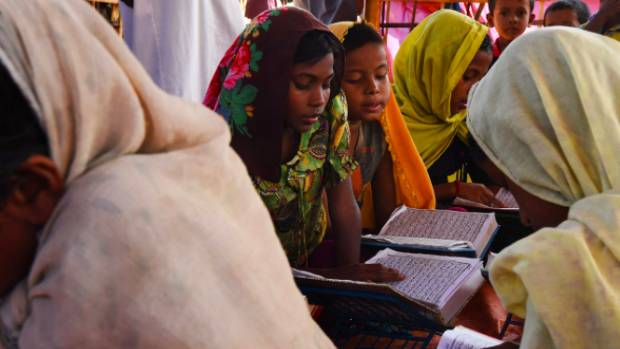 Girls read the Koran at a madrasa in Burma Para camp.