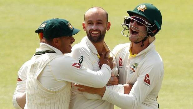 Australia captain Steve Smith (left) and team-mates rush to Nathan Lyon (centre) after the spinner snared the wicket of ...