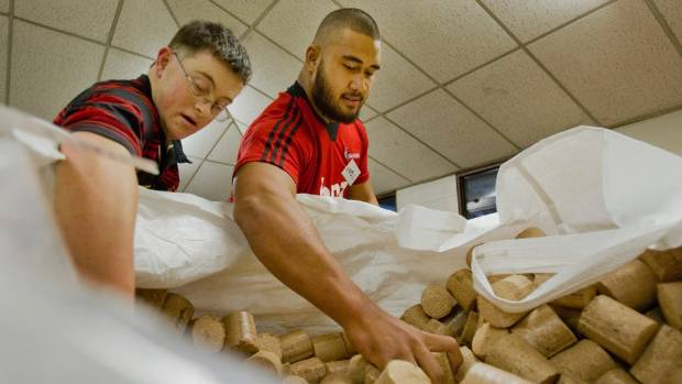 Crusader Nepo Laulala works with Daniel Forman bagging recycled wood for pellet fires while helping out at Kilmarnock ...