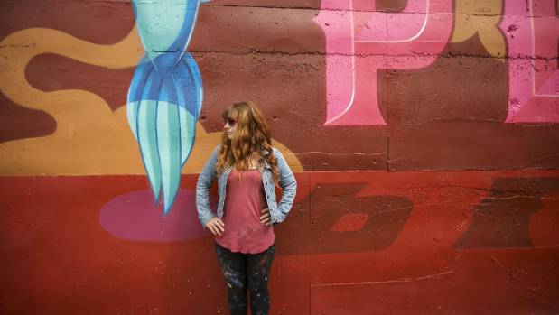 Street artist Kell Sunshine, seen here with a mural she painted on the wall of the Eruption Brewery in Lyttelton, will ...