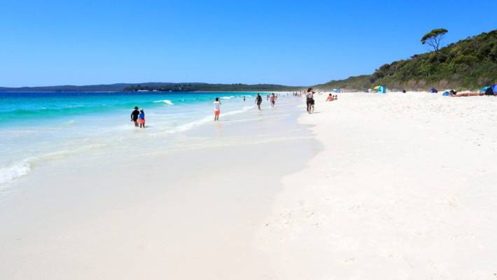 Tourists And Holidaymakers Enjoy The Sunshine Pristine Sands At Hyams Beach