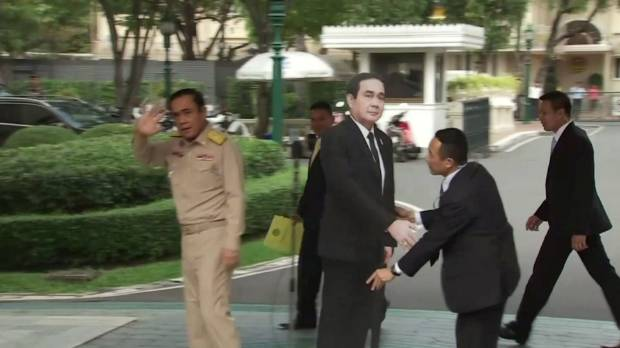 A life-sized cardboard cut-out figure of Thailand PM Prayuth Chan-ocha stands next to the microphone after he left the