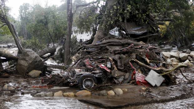 A car and debris were smashed against a tree along Hot Springs Road. Homes were swept from their foundations as heavy ...