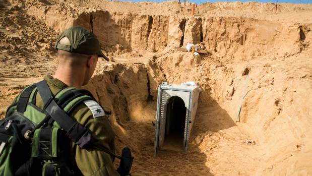 An Israeli soldier stands on the Israeli side of the border with Gaza near the opening of a tunnel that Israel says