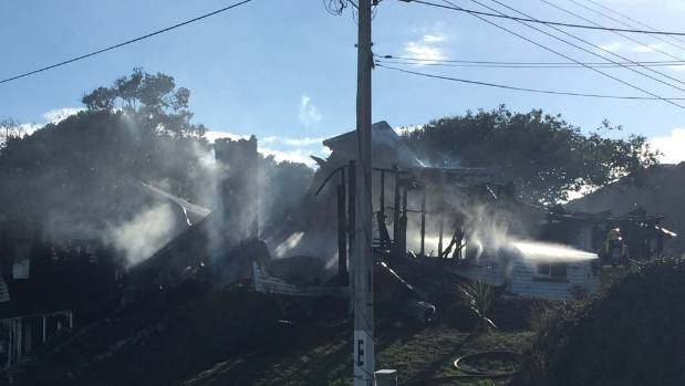 Firefighters dampen the remains of the house fire in Paekākāriki.