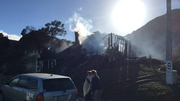 The aftermath of the house fire in Paekākāriki. with one of the homeowners being comforted in the foreground.