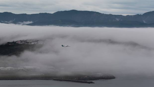 An Air New Zealand Flight Taking Off From Wellington Airport Through A Bank Of Fog About