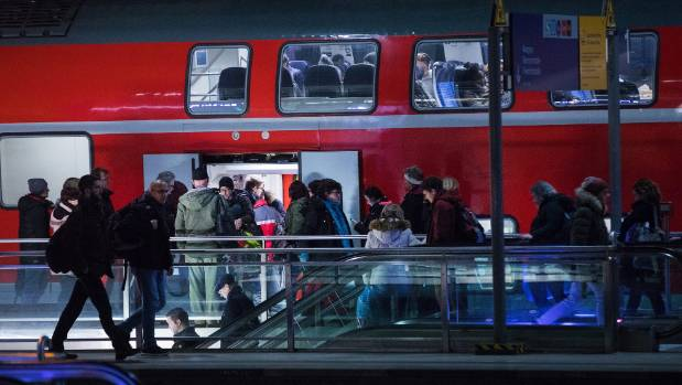 Commuters board a Regio train at a railway station in Berlin.