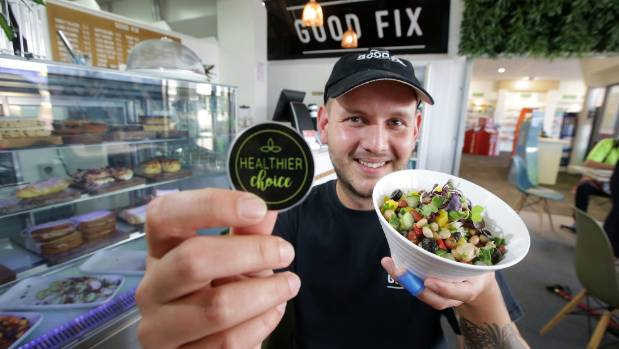 Good Fix cafe manager Harry Moss shows the Healthier Choice label the south City cafe is using to help customers make ...