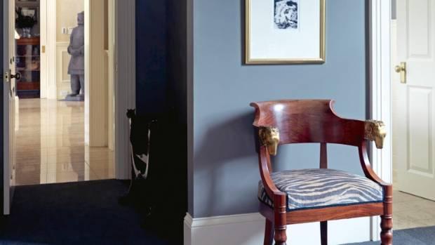 A gilded ram's head chair below a lithograph by Christchurch artist Philip Beadle.