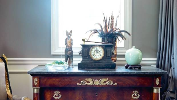 An old English slate clock sits atop a French polished Empire commode with a fossil stone top.