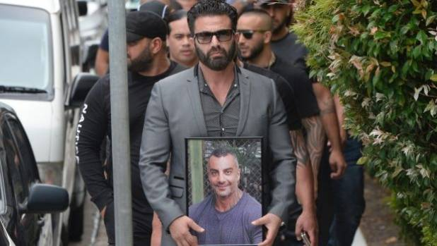 "A man carries a framed photo of Mahmoud ""Mick"" Hawi at the funeral."