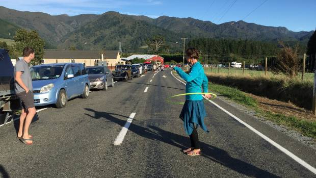 A woman hula hoops while she waits in the queue of cars waiting to cross the Takaka Hill.