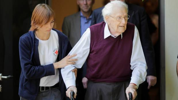 A Red Cross worker helps former SS guard Oskar Groening right leaves the court after the verdict of his trial