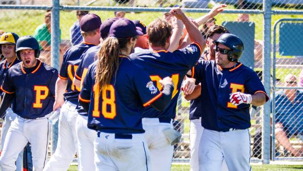 The Papanui Tigers congratulate home run hitter Anthony Stuart (R) after he put them ahead in the national softball ...
