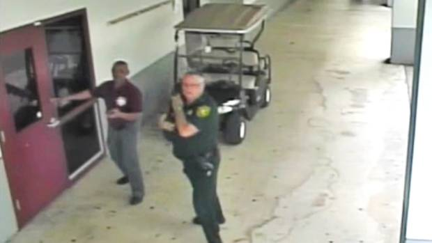 CCTV video footage shows sheriff's deputy Scot Peterson right waiting outside the school during the shooting