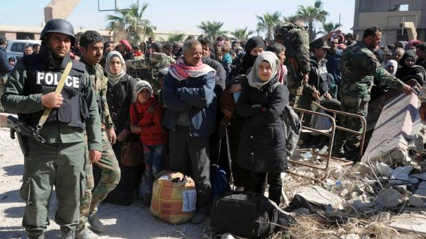Syrian troops stand guard as civilians stand with their belongings after fleeing from fighting between the Syrian